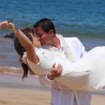 Couple celebrating their wedding with a kiss on a Maui beach.